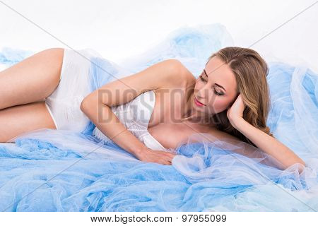 Girl Lying On Plume Of Her Long Dress With On A White Background