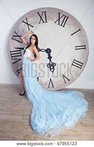 Girl In A Long Dress With Plume Standing Near The Huge Clock
