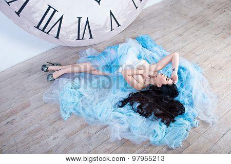 Beautiful Asian Girl Lying On The Floor On Her Dress Near The Huge Clock