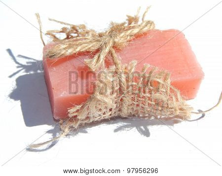 Pink bar of soap with shadow on white background