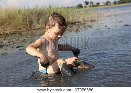Boy Sitting In The Healing Mud