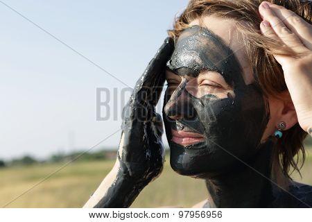 Woman Applying Black Healing Mud