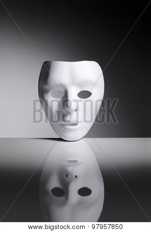 White blank plastic mask on reflective surface.