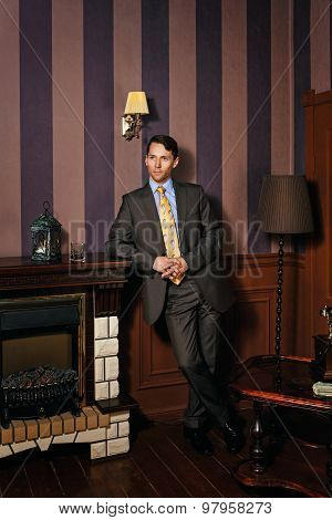 Businessman Standing By The Fireplace.