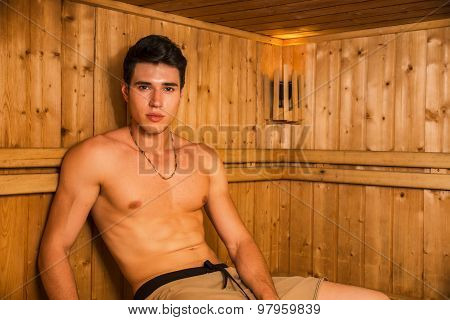 Young Man Relaxing in Sauna, Sitting on Wood Bench