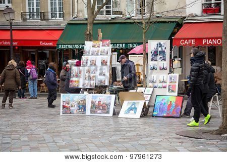 PARIS, FRANCE - MARCH 3RD: Street artists display their work in a cobbled market square in Montmartre, 18th Arrondissement. On March 3rd 2015.