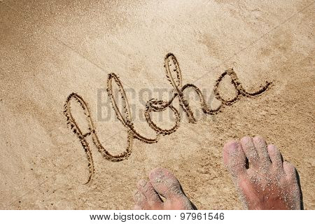 Concept or conceptual hand made or handwritten Aloha text in sand on a beach in an exotic island background with feet
