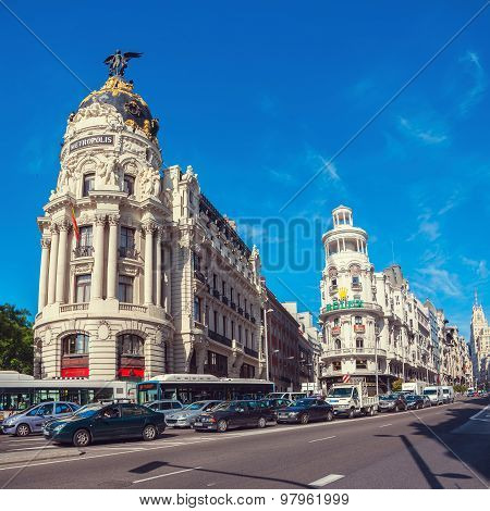 View of Gran Via street with cars and people in Madrid