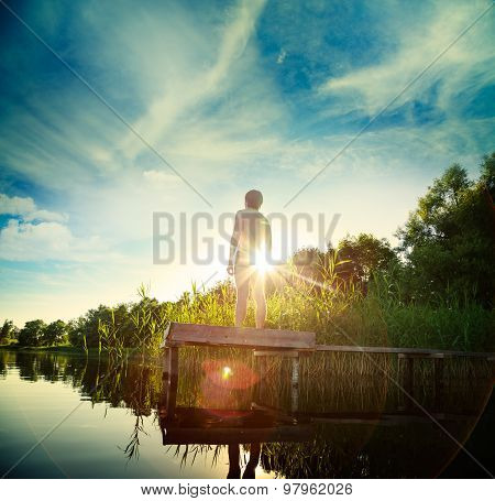 Young Man Standing on the Pier by Lake