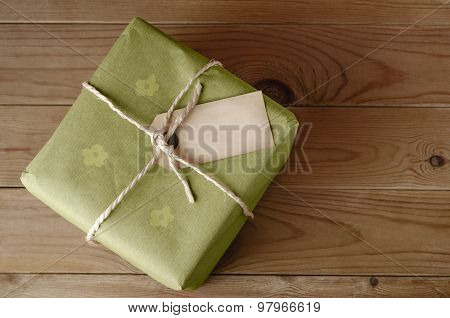String Tied Parcel With Label And Green Floral Wrapping Paper
