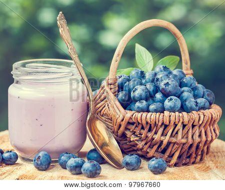 Fresh Blueberries Yogurt In Glass Jar And Wicker Basket With Bilberries.
