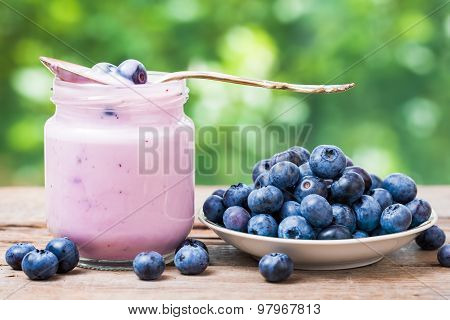 Fresh Blueberries Yogurt In Glass Jar And Saucer With Bilberries.
