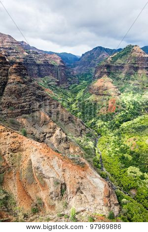 An overlook of Waimea canyon during a partly cloudy day shows the colorful, textured patterns of the rocky terrain.