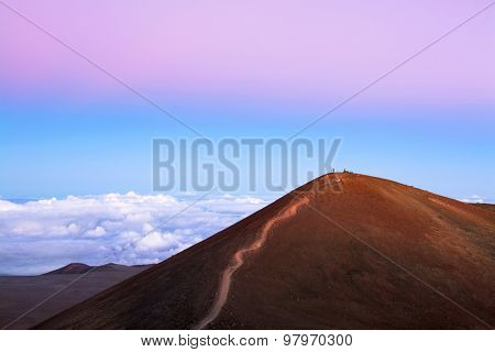 A red dirt mountain with a trail to the top at 14,000 feet overlooks the top of clouds and exposes the pink inversion layer typical of cold air environments.