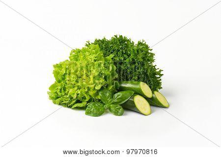 heap of fresh green vegetables on white background