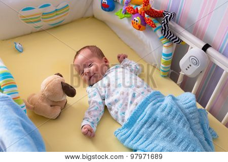 Baby boy lying down in the cradle