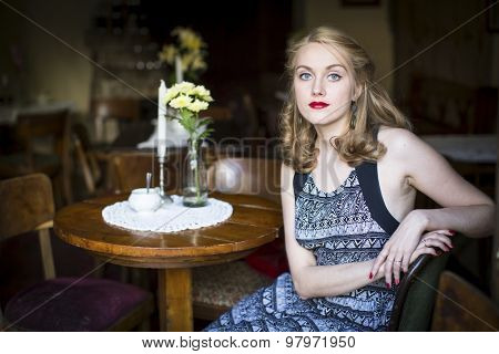 Portrait of young beautiful woman sitting the dim interior of the old cafe.