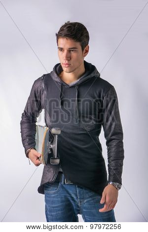 Handsome young man with skateboard under his arm