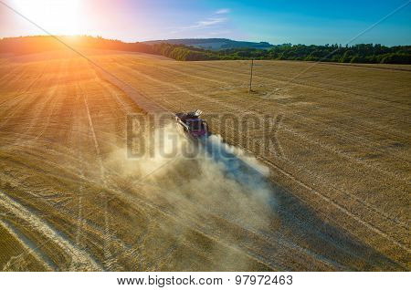Sunset Over The Combine Working On The Field