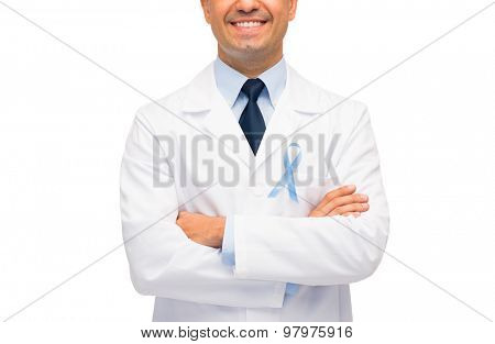 healthcare, profession, people and medicine concept - close up of smiling male doctor in white coat with sky blue prostate cancer awareness ribbon