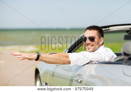 auto business, transport, leisure and people concept - happy man driving cabriolet car and waving hand outdoors