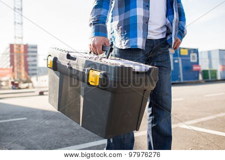 building, protective gear and people concept - close up of builder carrying toolbox at construction site