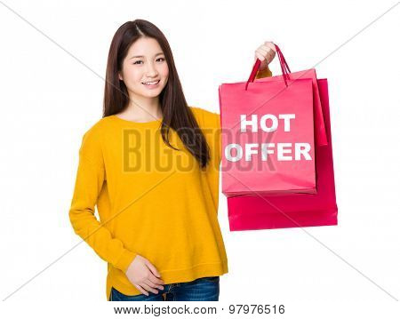 Woman hold with shopping bag showing hot offer