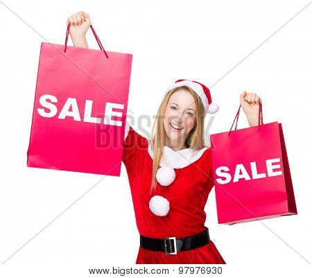 Woman with christmas party dress hold up with shopping bag and showing a word sale