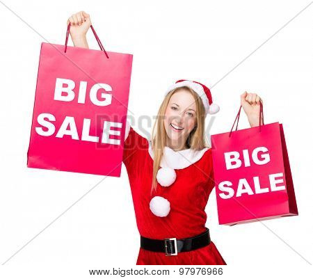 Woman with christmas party dress hold up with shopping bag and showing big sale