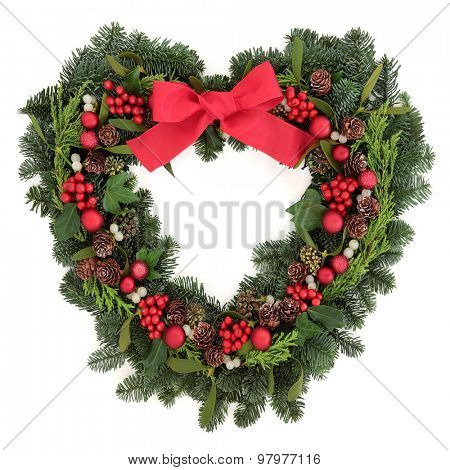 Christmas heart shaped wreath with red bauble decorations and bow, holly, mistletoe, ivy and winter greenery over white background.