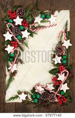 Christmas abstract background border with candy cane and gingerbread biscuits, holly, ivy, cedar cypress and fir on parchment paper over old oak wood.