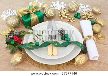 Christmas dinner place setting with plates, cutlery, napkin, baubles and ribbon gift decorations with winter flora over oak background.