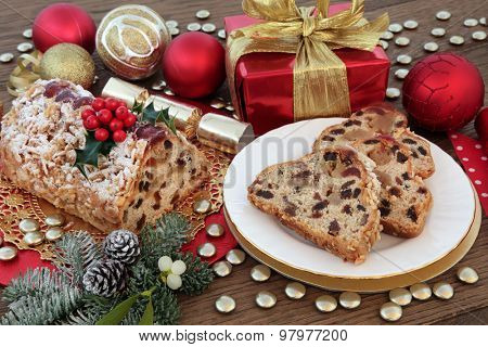 Christmas stollen cake with slices, red and gold decorations, holly, mistletoe and winter greenery.