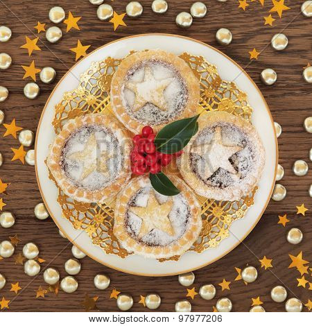 Homemade mince pies on a gold doilie and plate with holly over oak background with stars.
