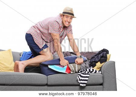 Young man packing a lot of clothes into one bag and looking at the camera isolated on white background