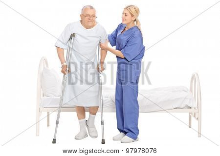 Full length portrait of a young female nurse helping a senior patient with crutches isolated on white background