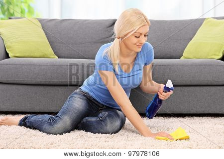 Young blond woman cleaning a carpet in front of a gray sofa with a rag at home