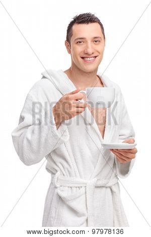 Vertical shot of a young man in a white bathrobe holding a cup of tea and looking at the camera isolated on white background