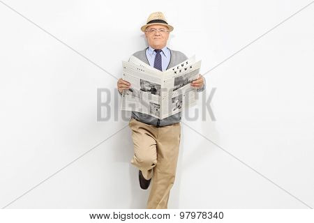 Senior gentleman holding a newspaper and leaning against a gray wall. The newspaper is custom made, text is Latin and the pictures are my copyright. Additionally property release uploaded.