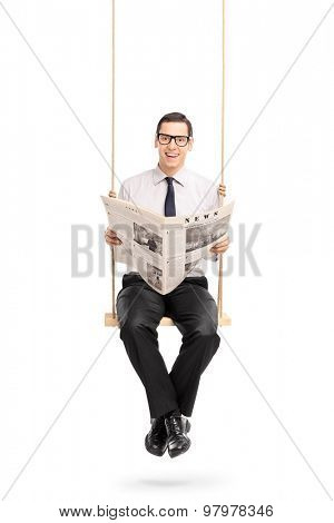 Vertical shot of a young man reading a newspaper seated on a swing and looking at the camera isolated on white background