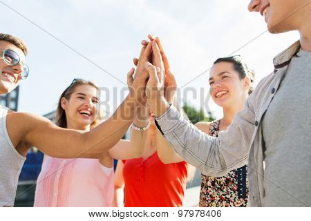 success, people, teamwork and gesture concept - close up of happy  friends hands making high five outdoors