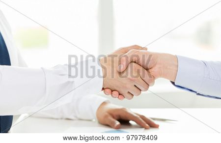 business, people, partnership, gesture and cooperation concept - close up of hands making handshake in office