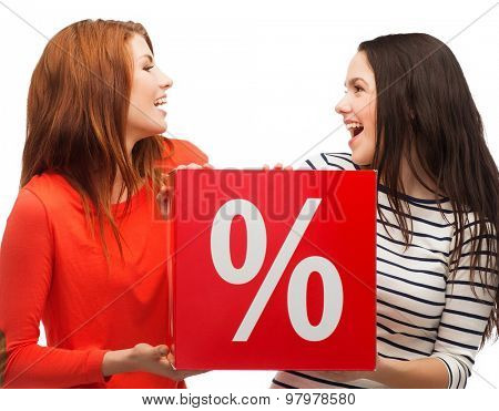 shopping, sale, and gift sconcept - two smiling teenage girls with percent sign on red box