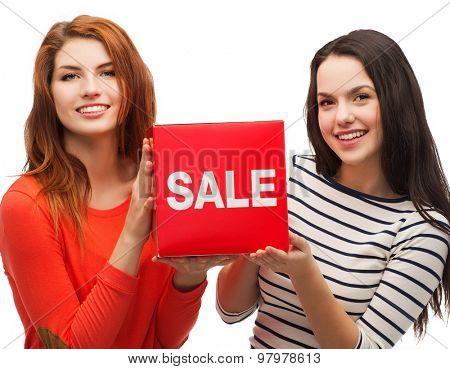 shopping, sale, and gift sconcept - two smiling teenage girls with sale sign on red box
