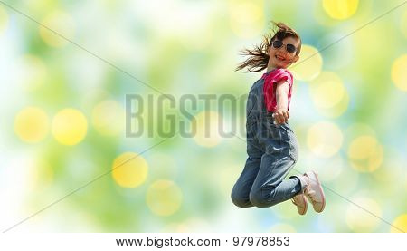 summer, childhood, leisure and people concept - happy little girl jumping high over green summer lights background
