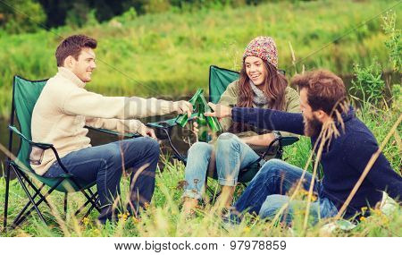 adventure, travel, tourism, friendship and people concept - group of smiling tourists clinking beer bottles in camping