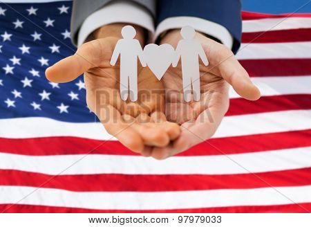 people, homosexuality, same-sex marriage and love concept - close up of happy male gay couple holding paper cutout love symbol over american flag background