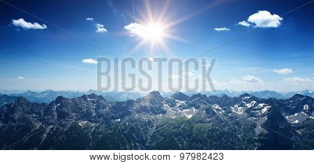 Mountainous scenic panoramic landscape with the sun shining bright over the Alps, at the border between Germany and Austria