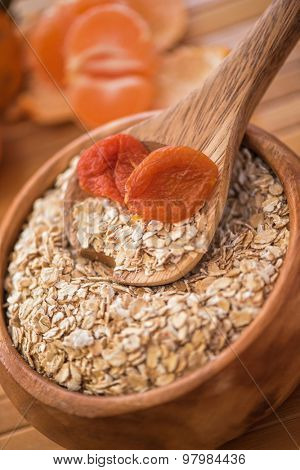 Oat flakes with  dried apricots at wooden plate on wooden background