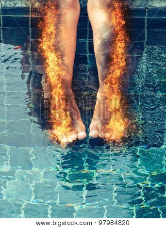 Woman with burning legs consumed in fiery orange flames and scorched skin dangling her legs over a swimming pool, healthcare concept